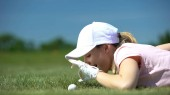 Cunning woman hitting golf ball in hole with finger, having fun during game