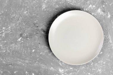 Top view of matte round empty plate on dark background.
