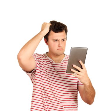 thinking guy looks at the tablet and scratches his head with his hand. emotional guy isolated on white background.