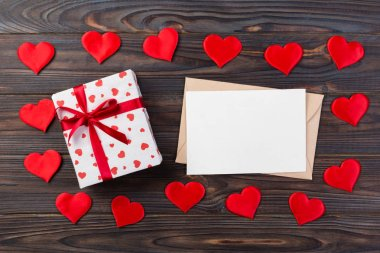 Envelope Mail with Red Heart and gift box over Dark Wooden Background. Valentine Day Card, Love or Wedding Greeting Concept.