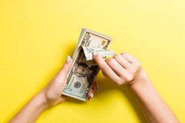 Para sayan kadın ellerinin en iyi görünümü. Renkli arka plan üzerinde çeşitli dolar banknotlar. Maaş kavramı. Rüşvet kavramı