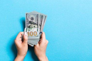 Para sayan kadın ellerinin en iyi görünümü. Renkli arka planda 100 dolarlık banknotlar. İş kavramı