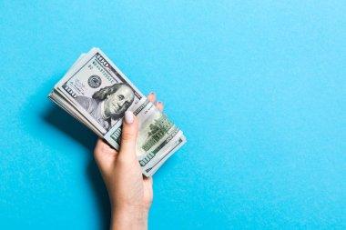 Renkli arka planda kadın elinde yüz dolarlık banknotlar demeti. Kopyalama alanı ile finans ve iş kavramı