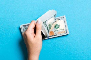 Renkli arka planda yüz dolarlık banknotlar sayan bir iş kadınının ellerinin en iyi görünümü. Kopya alanı ile başarı ve zenginlik kavramı