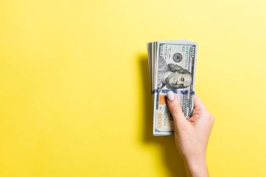 100 dolarlık banknotlar, fotokopi çekilen ellerde. Renkli arkaplanda para tasarrufu kavramının üst görünümü
