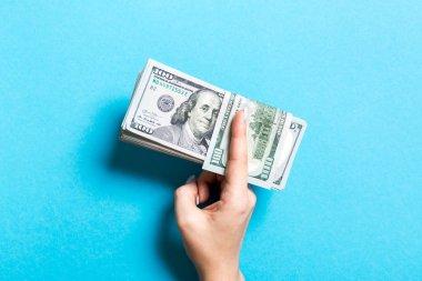 Kadın el renkli arka plan üzerinde yüz dolarlık banknotlar bir demet tutan. Maaş ve ücret kavramı