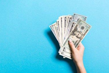 Renkli arka planda çeşitli dolar banknotları veren kadın elin üst görünümü. Kopyalama alanı ile sadaka ve bağış kavramı