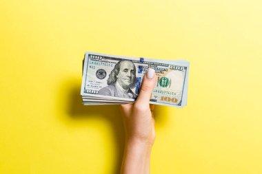 Kadın eli renkli arka planda 100 dolarlık banknotlar veriyor. Sadaka ve bağış konsepti
