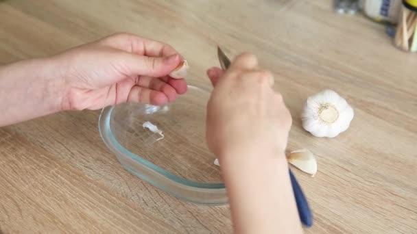 dívka oloupe česnek nožem v kuchyni. žena počítala česnek v palci na kuchyňském stole