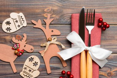 Top view of flatware tied up with ribbon on napkin on wooden background. Close up of christmas decorations and reindeer. New Year holiday concept.
