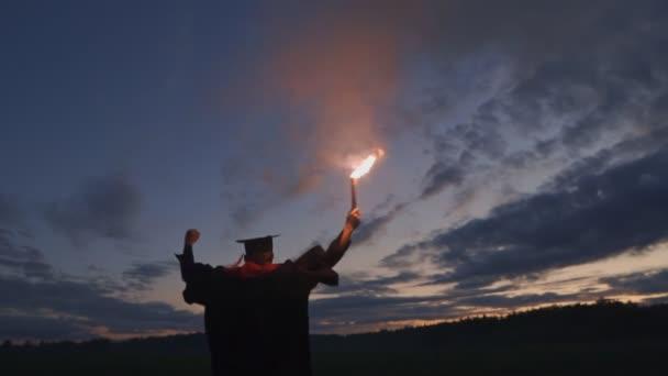 Šťastný absolvent v šatech a čepici mává ohňostrojem.