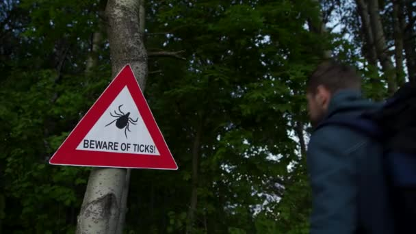 Muž vejde do lesa, kde na stromě visí varovná cedule Pozor na klíšťata