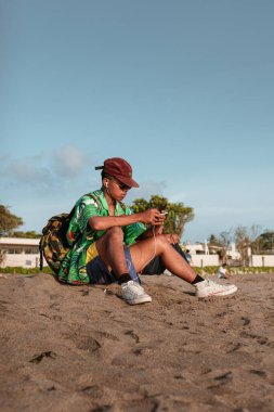 Asian guy in a green shirt and cap sits on the beach and listens to music