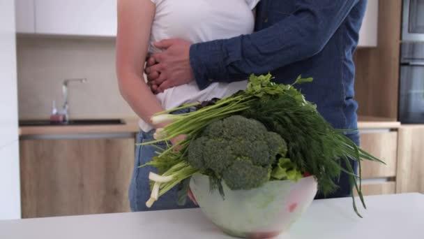 Fiatal pár ölelkezve egy modern konyhában.Egészséges táplálkozás és diéta.