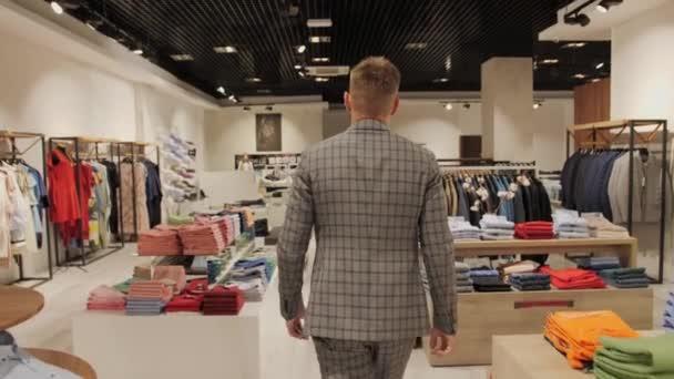 Stylový muž v šedém obleku jde do pánského obchodu s oblečením pohled zezadu na pozadí obchodu.