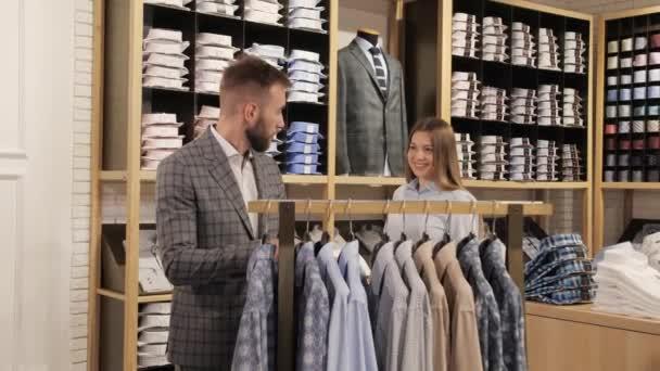 Ženský konzultant pomáhá kupujícímu vybrat si tričko v obchodě se značkovým oblečením.