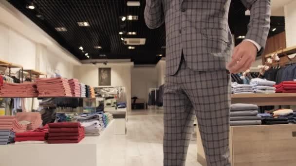 Stylový obchodník v šedém obleku mluví po telefonu v pánském obchodě s oblečením.