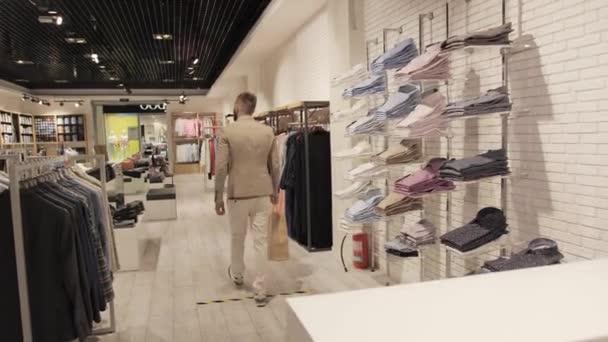 Spokojen zákazník po nakupování s taškou v ruce opouští sklad značkového oblečení.