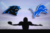 Carolina Panthers vs. Detroit Lions. NFL Game. American Football League match. Silhouette of professional player celebrate touch down. Screen in background.