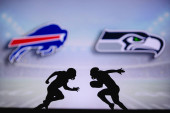 Buffalo Bills vs. Seattle Seahawks. NFL match poster. Two american football players silhouette facing each other on the field. Clubs logo in background. Rivalry concept photo.