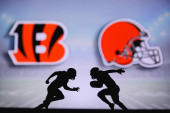 Cincinnati Bengals vs. Cleveland Browns. NFL match poster. Two american football players silhouette facing each other on the field. Clubs logo in background. Rivalry concept photo.