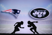 New England Patriots vs. New York Jets. NFL match poster. Two american football players silhouette facing each other on the field. Clubs logo in background. Rivalry concept photo.