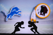 Detroit Lions vs. Washington Redskins. NFL match poster. Two american football players silhouette facing each other on the field. Clubs logo in background. Rivalry concept photo.