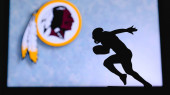 Washington Redskins. Silhouette of professional american football player. Logo of NFL club in background, edit space.