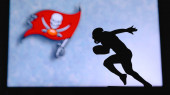 Tampa Bay Buccaneers. Silhouette of professional american football player. Logo of NFL club in background, edit space.