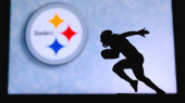 Pittsburgh Steelers. Silhouette of professional american football player. Logo of NFL club in background, edit space.