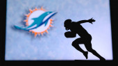 Miami Dolphins. Silhouette of professional american football player. Logo of NFL club in background, edit space.