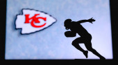 Kansas City Chiefs. Silhouette of professional american football player. Logo of NFL club in background, edit space.