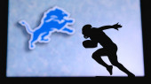 Detroit Lions. Silhouette of professional american football player. Logo of NFL club in background, edit space.