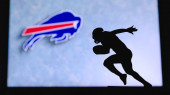 Buffalo Bills. Silhouette of professional american football player. Logo of NFL club in background, edit space.