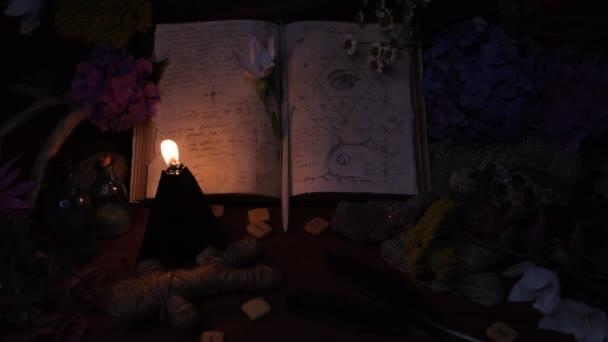 Weißer Ziegenschädel mit Hörnern, aufgeschlagenes altes Buch, Runen, schwarze Kerzen auf dem Hexentisch. Okkultes, Esoterisches, Wahrsagerisches und Zauberhaftes. Halloween, Tag des toten Konzepts.