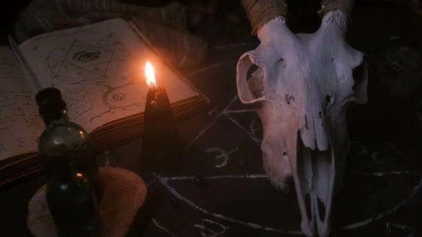 Weißer Ziegenschädel mit Hörnern, aufgeschlagenes altes Buch, Runen, schwarze Kerzen auf dem Hexentisch. Okkultes, Esoterisches, Wahrsagerisches und Zauberhaftes. Halloween-Konzept.
