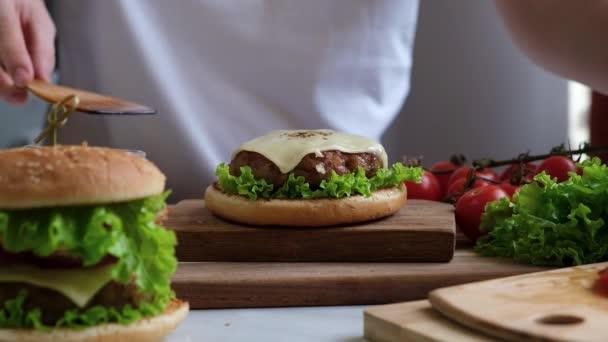 Proces vaření šťavnatý domácí burger - skládání složek dohromady krok za krokem. Šéf připravuje rychlé občerstvení.