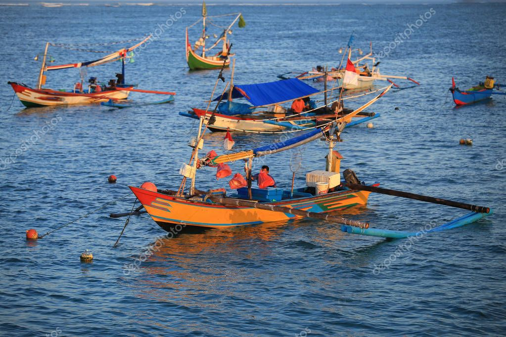Asian fisherman on colorful handcrafted Balinese fishing boat at port in Jimbaran beach, Bali