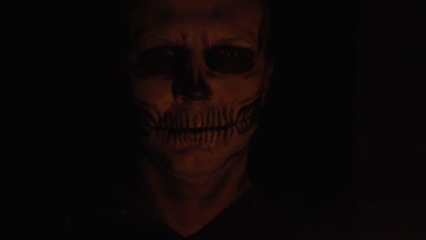 Makeup kostra na Halloween. Mužská kostra v matném světle svíčky se dívá do kamery. Tmavé pozadí. Vysoce kvalitní 4K záběry
