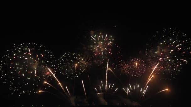 Goldenes großes, glänzendes Feuerwerk mit Bokeh-Lichtern am Nachthimmel. Glühendes Feuerwerk Silvesterfeuerwerk. Feuerwerksfest.
