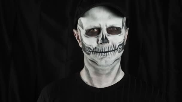 Schminkskelett für Halloween. Menschliches Skelett auf dunklem Hintergrund. Ein Mann zeigt eine Herzform in seinen Händen.