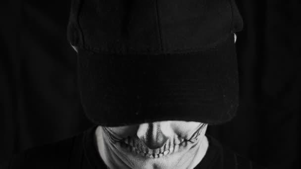 Muž s make-up kostrou a černou čepicí na tmavém pozadí. Halloween nebo horor. Vysoce kvalitní 4K záběry