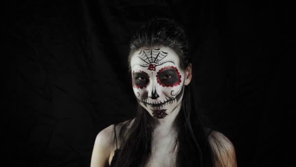 Halloween-Maske Calavera Catrina. Mädchen mit einer Rose in der Hand. Mexikanischer Tag der Toten. Porträt einer jungen Frau mit schrecklich buntem Make-up für Halloween auf dunklem Hintergrund. 4K.