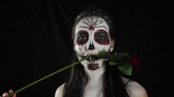 Halloween-Make-up. Mädchen mit einer Rose. Porträt einer jungen Frau mit schrecklich buntem Halloween-Make-up auf dunklem Hintergrund.