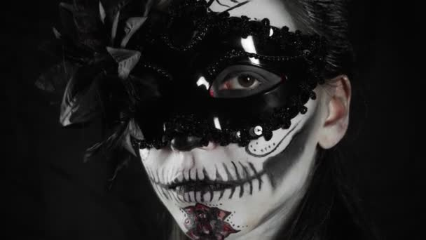 Mexický den mrtvých. Mladá žena s cukrovou lebkou Halloween make-up se dívá do kamery. Šťastný Halloween. Vysoce kvalitní video 4k