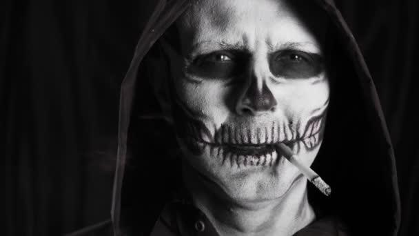 Muž s maskérskou kostrou a černou kápí na tmavém pozadí. Kostlivec kouří cigaretu. Kouření zabíjí. Halloween nebo horor. Vysoce kvalitní video 4k