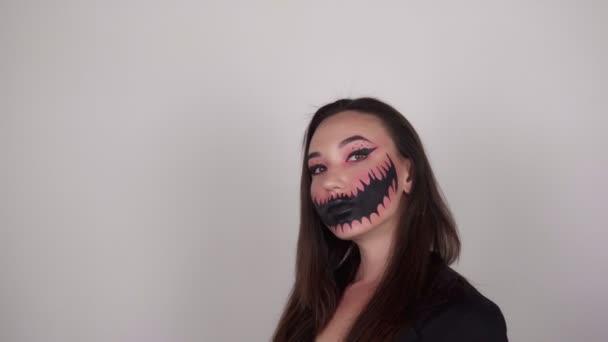 Schöne Frau mit gruselig geschminktem Gesicht zu Halloween, die auf die Kamera zugeht. Hochwertiges 4k Filmmaterial