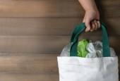 Mädchen hält Leinwand Einkaufstasche auf Holz Hintergrund hingegen sparen Umwelt und Recycling Konzept