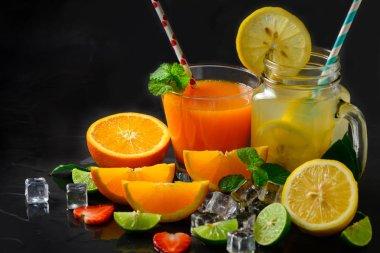 Orange juice and lemon juice with fresh slice orange and slice lemon on black stone background, summer drinks concept