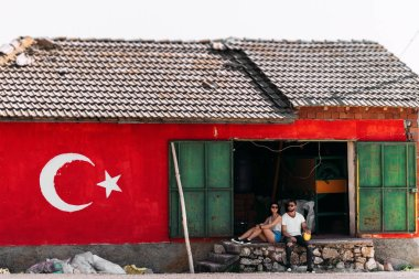 Man and woman are sitting near the barn. Travel to Turkey. Honeymoon trip. Guy and girl traveling. Newly married couple. Patriots. Picture on the wall. Country flag on the wall. Couple hitchhiking